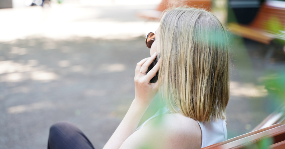 A woman talking to a mobile phone in the park, summer (Photo: Ministry of Transport and Communications)
