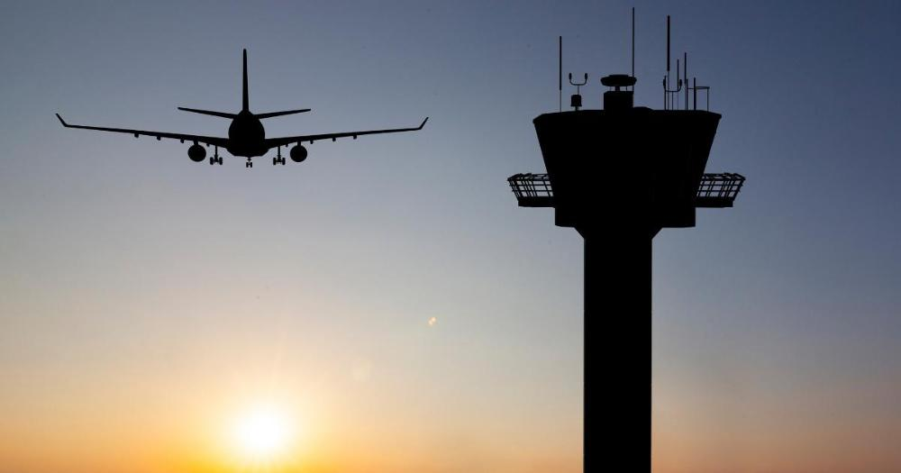 Aeroplane in air and control tower in the evening (Photo: Shutterstock)